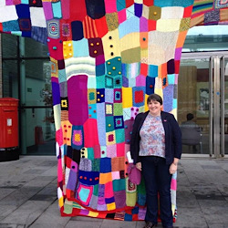 Sharon standing in front of a huge piece of guerilla knitting